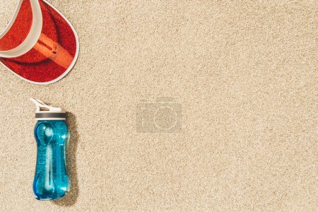 top view of red cap and water bottle on sand