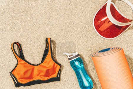 flat lay with arrangement of cap, female sportswear, mat and water bottle on sand
