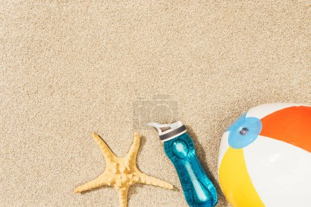flat lay with arranged water bottle, sea star and beach ball on sand