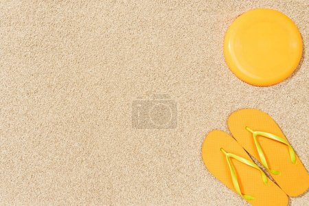 top view of yellow flip flops and frisbee on sand