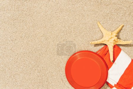 top view of sea star, red frisbee and towel on sand