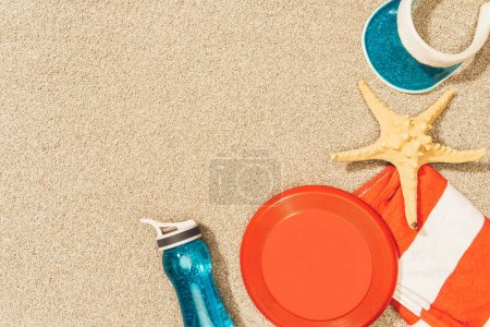 flat lay with water bottle, towel, cap, frisbee and sea star on sand