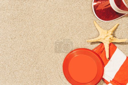 flat lay with red cap, flying disk, towel and sea star on sand