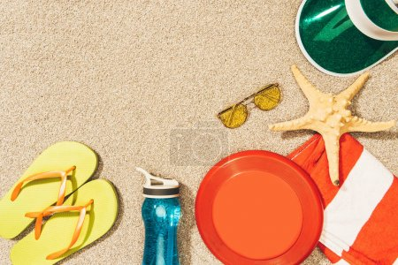 flat lay with frisbee, cap, flip flops, sunglasses and water bottle arranged on sand