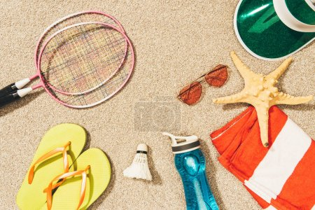 top view of badminton equipment, sunglasses, flip flops, cap and towel on sand
