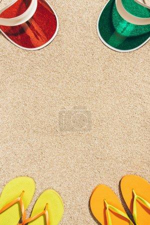 vista superior de tapones coloridos dispuestos y chanclas en la arena
