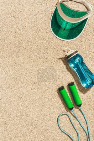 top view of arranged cap, water bottle and jump rope on sand