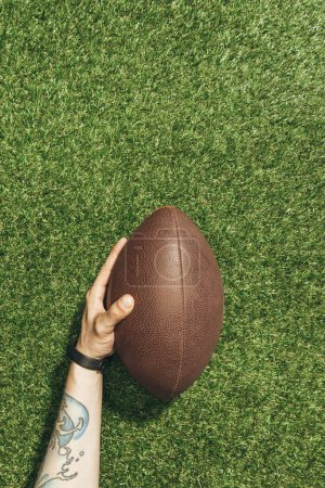 cropped shot of man holding rugby ball in hand on green lawn background