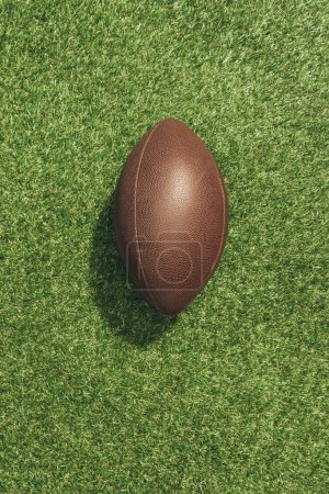 top view of american football ball on green lawn