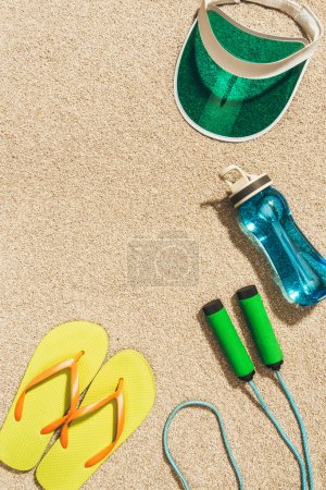 top view of arranged cap, flip flops, water bottle and jump rope on sand