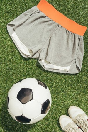 flat lay with soccer ball, sportswear and sneakers on green grass
