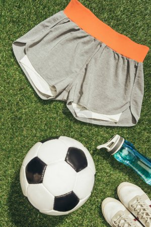 flat lay with soccer ball, sportswear, water bottle and sneakers on green grass
