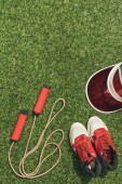 top view of arranged jump rope, cap and sneakers on green grass
