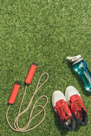 top view of arranged water bottle, skipping rope and sneakers on green grass