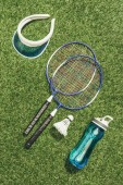 top view of badminton equipment, water bottle and cap on green grass