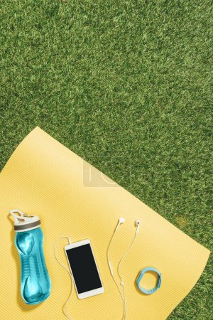 flat lay with water bottle, watch, smartphone and earphones on yellow mat on green lawn
