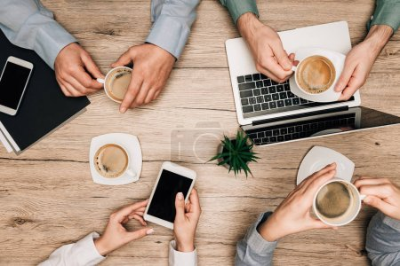 Photo for Top view of business partners drinking coffee by gadgets on table, cropped view - Royalty Free Image