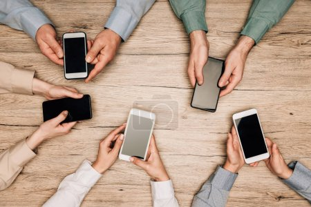 Photo for Top view of business people holding smartphones with blank screens on table, cropped view - Royalty Free Image