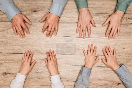 Photo for Top view of businesspeople with hands on wooden table, cropped view - Royalty Free Image