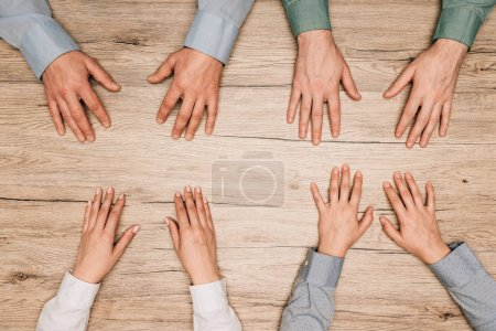Top view of businesspeople with hands on wooden table, cropped view