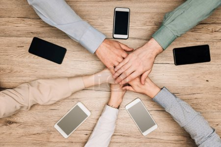 Photo for Top view of business partners holding hands by smartphones on table, cropped view - Royalty Free Image