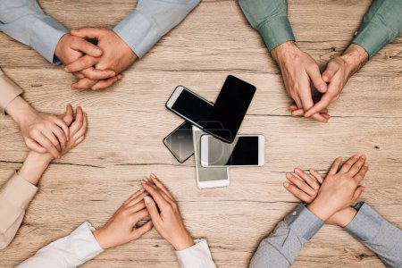 Photo for Top view of businesspeople at table with smartphones, cropped view - Royalty Free Image