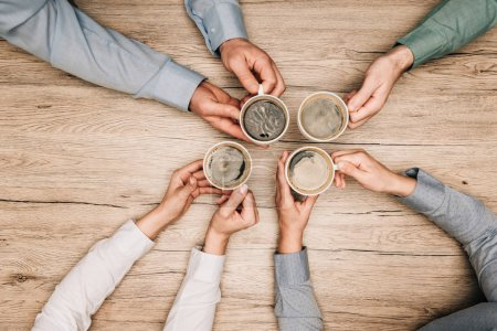 Top view of colleagues drinking coffee at wooden table, cropped view