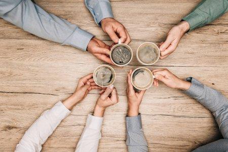 Photo pour Vue du dessus des collègues buvant du café à table en bois, vue dégagée - image libre de droit