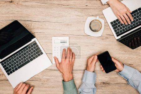 Photo pour Vue de dessus des partenaires d'affaires travaillant avec des ordinateurs portables, calculatrice et smartphone à la table en bois - image libre de droit