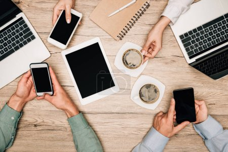 Photo for Top view of business partners using gadgets beside coffee on table, cropped view - Royalty Free Image
