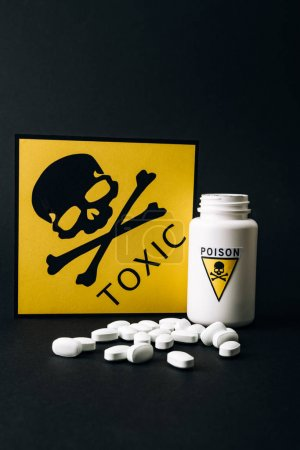 Photo pour Pilules par bouteille avec signe empoisonné et carte avec symbole toxique isolé sur noir - image libre de droit