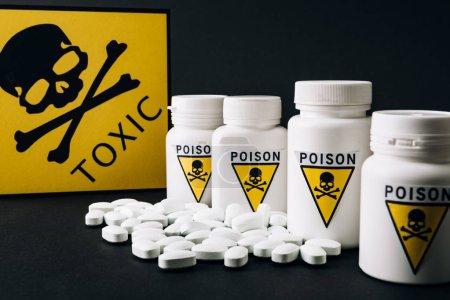 Photo pour Pots avec symbole poison par signe toxique et pilules isolées sur noir - image libre de droit