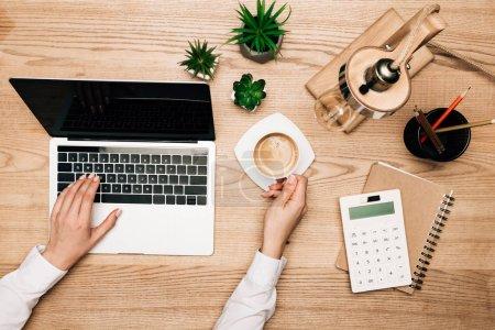 Photo pour Vue du dessus de la femme d'affaires travaillant sur un ordinateur portable tout en buvant du café par calculatrice sur la table, vue recadrée - image libre de droit
