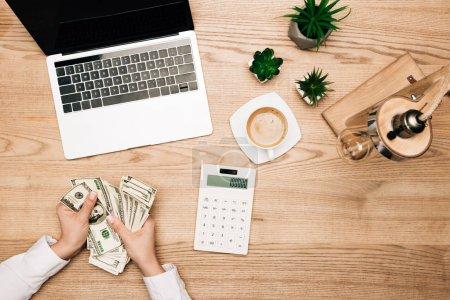 Photo pour Vue du dessus de la femme d'affaires tenant des billets en dollars par ordinateur portable et calculatrice sur la table - image libre de droit