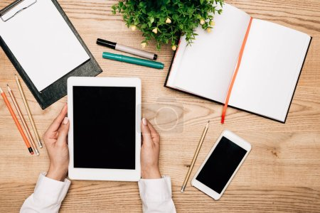 Photo for Top view of businesswoman holding digital tablet by smartphone and stationery on table, cropped view - Royalty Free Image