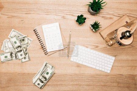 Foto de Vista superior de los billetes en dólares con calculadora y teclado de computadora en la mesa de madera. - Imagen libre de derechos