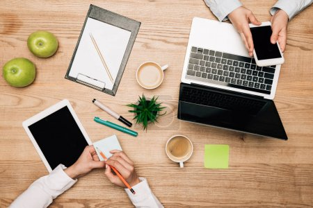 Photo pour Vue de dessus des partenaires commerciaux avec des appareils numériques, des notes collantes et du café sur la table, vue recadrée - image libre de droit