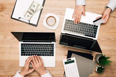 Vue du dessus des partenaires commerciaux utilisant des ordinateurs portables avec carte de crédit par dollar billets sur table en bois, vue recadrée