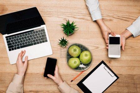 Photo pour Vue du dessus des hommes d'affaires utilisant des smartphones et un ordinateur portable par pommes et presse-papiers sur la table - image libre de droit