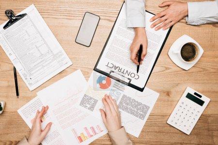 Photo pour Vue d'ensemble des gens d'affaires travaillant avec des contrats et des documents par calculatrice et café sur table - image libre de droit