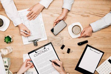 Photo pour Vue de dessus des partenaires commerciaux avec contrat, paperasse et café sur table en bois - image libre de droit