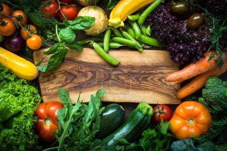 Photo pour Cadre de légumes crus autour de la planche à découper. Légumes fermiers biologiques. Vue de dessus. Concept alimentaire végétarien . - image libre de droit