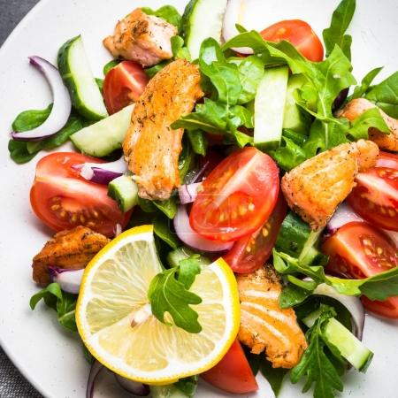 Photo for Fresh salad with salmon fish, arugula, tomatoes, cucumber and onion in white plate. Top view. - Royalty Free Image
