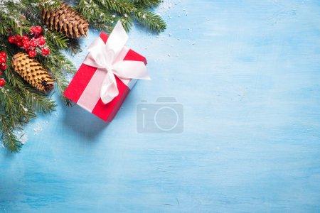 Photo pour Fond de Noël ou carte de voeux. Coffret cadeau de Noël rouge, branche de sapin et décorations sur bleu. Vue supérieure avec espace de copie . - image libre de droit