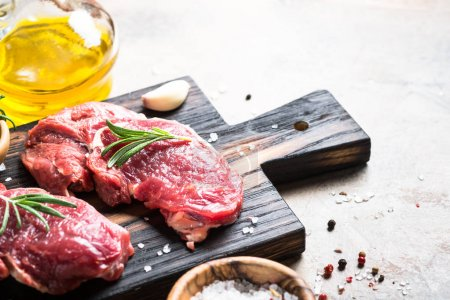 Photo for Raw meat. Beef steak rib eye on a cutting board with rosemary and spices. Top view copy space. - Royalty Free Image
