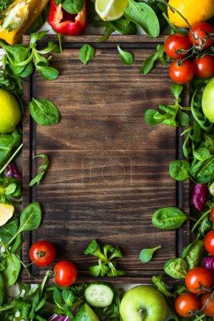 Foto de Fondo de alimentos saludables. Marco de la comida. Hojas frescas y verduras y tabla de cortar para su texto. Vista superior copia espacio - Imagen libre de derechos