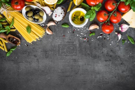 Photo for Italian Food background on black stone table. Pasta Olive oil spices herbs and tomato. Ingredients for cooking. Top view with copy space. - Royalty Free Image