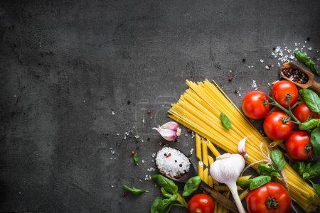 Photo pour Fond de la cuisine italienne sur la table en pierre noire. Pâtes d'huile d'Olive épices herbes et tomates. Ingrédients pour la cuisson. Vue de dessus copie espace. - image libre de droit