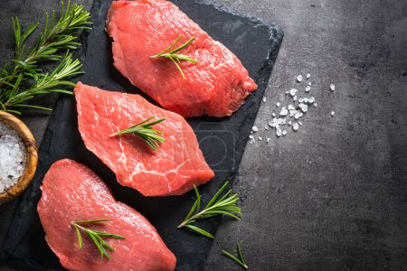 Photo for Raw meat. Fresh beef steak with rosemary and spices on black background. Top view copy space. - Royalty Free Image