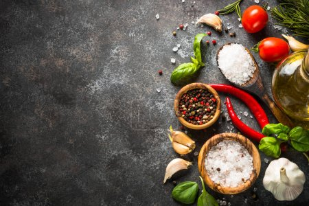 Photo for Food background. Olive oil, herbs, spices and vegetables on a dark stone table. Ingredients for cooking, Top view, Copy space. - Royalty Free Image